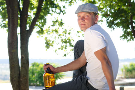 Man sitting relaxing in a rural landscape with a bottle of alcohol clutched in his hand turning to look at the camera with a serious expression Stock Photo