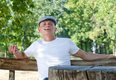 puffing: Man puffing on a cigarette while relaxing outdoors sitting on a rustic wooden bench in a park