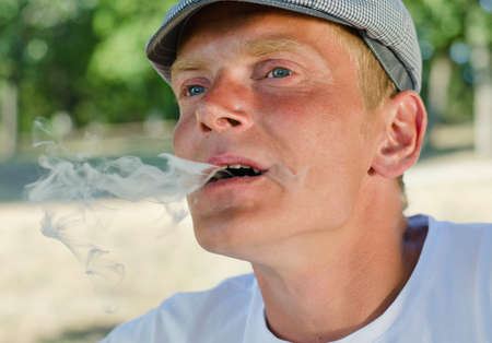 Close up of a man blowing smoke out of his mouth as he exhales while smoking a cigarette outdoors in the park photo
