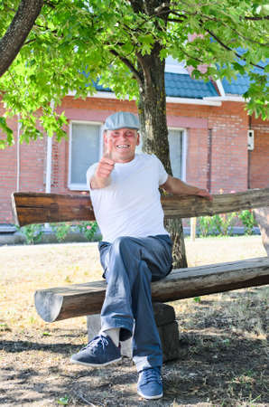 natty: Grinning good looking man in a natty cap giving a thumbs up of approval as he sits relaxing on a rustic wooden bench outside his home