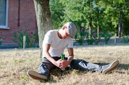 bowed head: Drunk man clutching a bottle of alcohol between his hands as he sits against a tree in the garden with his head bowed Stock Photo