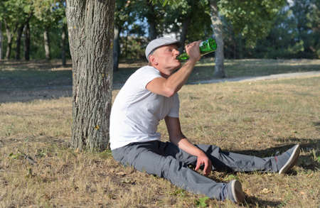 risky behavior: Alcoholic sitting drinking in a park swigging spirits directly from a bottle as he seeks to fill his craving and addiction