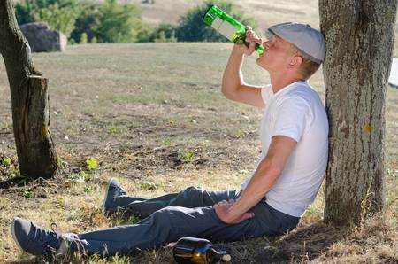 risky behavior: Alcoholic drinking alone in the countryside sitting on the ground with his back against a tree gulping spirits from a bottle