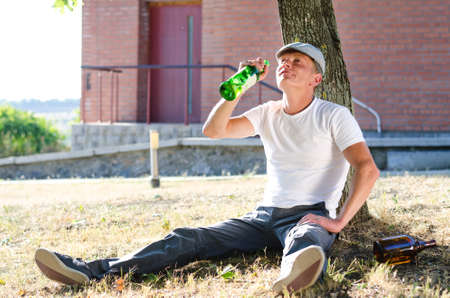 risky behavior: Man with an alcohol problem drinking spirits from a bottle sitting alone in a park or garden leaning against a tree in the summer sunshine Stock Photo