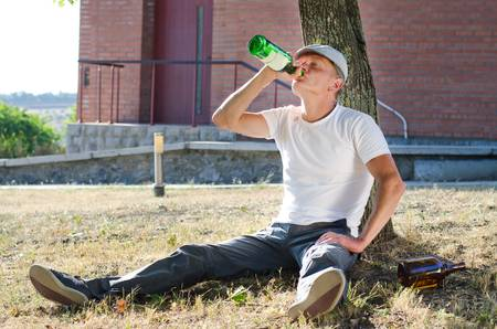 risky behavior: Alcoholic with a drink problem relaxing outdoors against a tree with a bottle of spirits gulping down the contents to satiate his craving and addiction