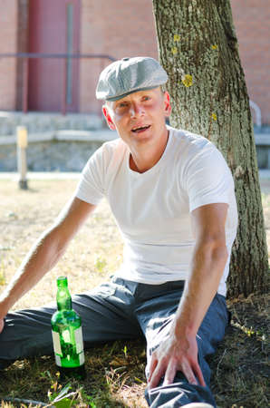 risky behavior: Happy drunk sitting comfortably on the grass leaning on a tree with a bottle of booze in front of him smiling at the camera