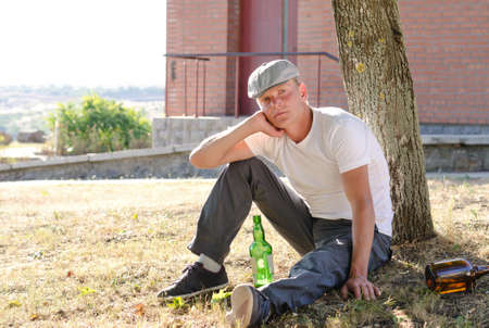 risky behavior: Alcoholic sitting thinking on the grass with his back to a tree surrounded by empty and half full bottles of alcohol Stock Photo