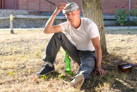 risky behavior: Drunk man sitting at the base of a tree with a bottle of alcohol in front of him and discarded bottles at the side staring morosely ahead of himself Stock Photo