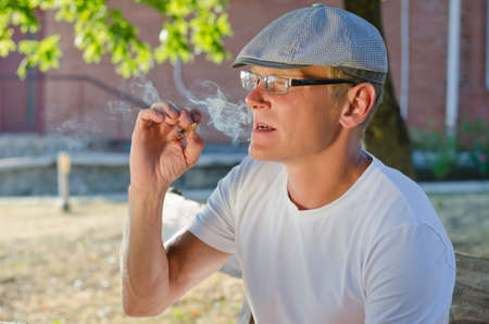 Man wearing glasses and a cap relaxing and sitting outdoors smoking a cigarette or joint of marijuana or cannabis photo