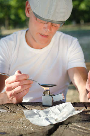 risky behavior: Man with a hardline drug addiction heating drugs in a spoon over a flame while sitting alone outside