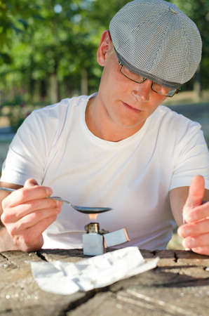 risky behavior: Drug addict getting ready to shoot up sitting at a table in a park heating the illegal drugs in a spoon over a flame