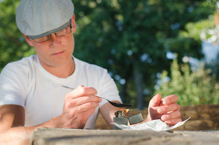 risky behavior: Man disolving heroin with a lighter in the outdoors