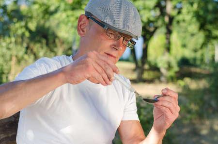 druggie: Verticale ritratto di un uomo caucasico dipendente riempire una siringa con eroina solubile riscaldata all'aperto