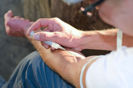 intravenously: Close-up rear view of an addicted man injecting heroin intravenously into his left arm tied with a belt Stock Photo