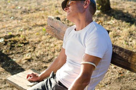 druggie: Addicted caucasica uomo seduto su una panchina in effetti la sensazione parco collaterali dopo l'iniezione di una dose di droga per via endovenosa