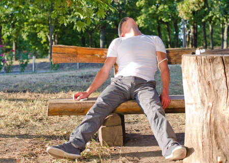 fainted: Addicted man sitting fainted on a bench in the park experiencing the side effects of heroin