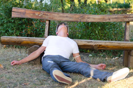 druggie: Uomo di mezza et� sdraiato per terra con la testa appoggiata su un banco di sentirsi male a causa di abuso di droga Archivio Fotografico