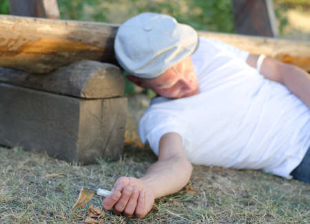 intravenously: Addicted Caucasian man fainted on the ground after taking an overdose intravenously next to a bench in the park