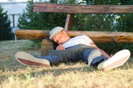 druggie: L'uomo caduto in possesso di un siringa, per terra accanto a una panchina nel parco Archivio Fotografico