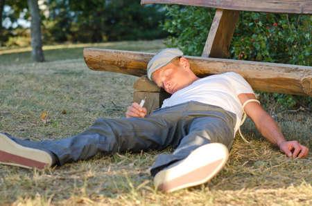 druggie: Uomo Addicted caduto in possesso di un siringa, per terra accanto a una panchina nella corteccia