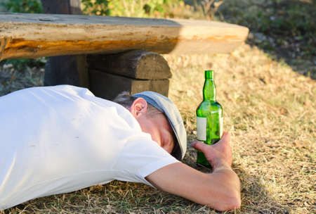 timber bench seat: Drunk man holding a bottle of alcoholic beverage sleeping on the ground next to a bench in the park in summer Stock Photo