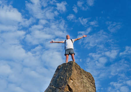 Man celebrating reaching the top of a mountain standing on top of a high rock pinnacle with his arms outstretched rejoicing photo