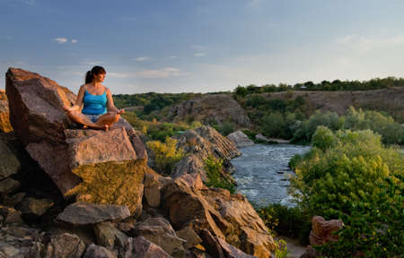 tranquillity: Attractive middle-aged woman sitting cross-legged meditating on a rock above a mountain valley and river as she enjoys the tranquillity of nature