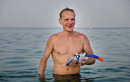 waist deep: Laughing middle-aged man with goggles and a snorkel in his hands standing waist deep in the sea as he finishes skindiving on his summer vacation
