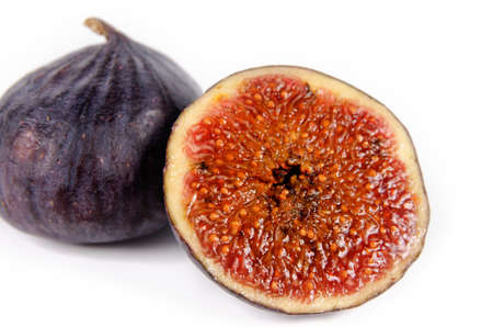 purple fig: Juicy ripe purple fig with a whole fresh fig and halved portion in the foreground showing the texture of the seeds