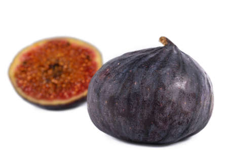purple fig: Juicy ripe purple fig with a whole fresh fig and halved portion in the foreground Stock Photo