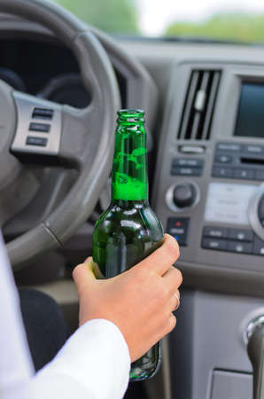steers: Conceptual image of the hand of a woman drinking alcohol and driving holding a green glass bottle of liquor in her hand as she steers the car
