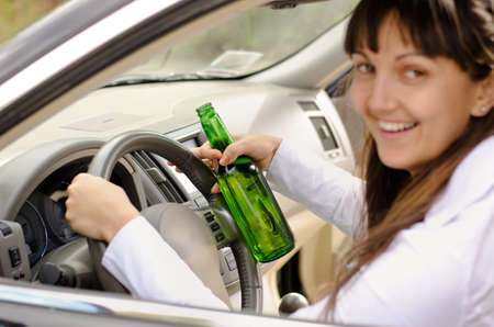 addictive drinking: Female driver drinking and driving while grinning out of the side window as she clutches the steering wheel with her bottle of alcohol clasped in one hand