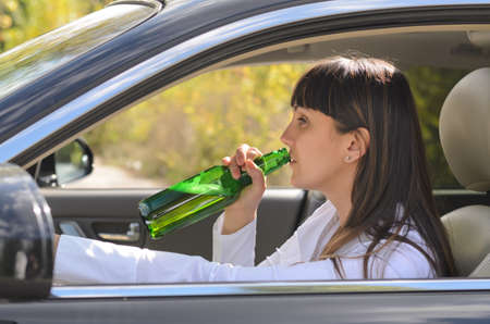 incapacitated: Alcoholic woman drinking and driving raising the bottle to her lips to take a swig as she steers the car, view through the side window Stock Photo
