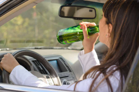 steers: Woman drinking alcohol and driving raising the bottle to her lips to take a swig as she steers the car, view through the side window