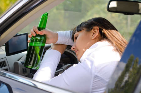 Passed out: Alcoholic woman driver passed out in the car with her head resting on her arm on the steering wheel and her bottle of booze clasped in her hand Stock Photo
