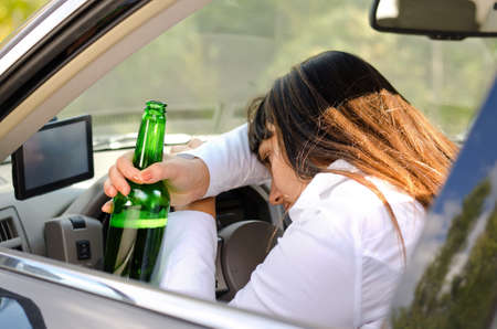 incapacitated: Drunk woman driver passed out in the car with her head resting on her arm on the steering wheel and her bottle of booze clasped in her hand