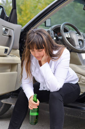 incapacitated: Alcoholic woman driver stopping for a drink of bear from a a bottle sitting on the sill in the open door of her car with her head resting on her hand