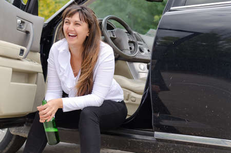 incapacitated: Happy woman drunkard in a car sitting on the sill of the open drivers door clasping her bottle of spirits and laughing