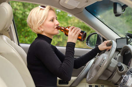 Young attractive blond female driver drinking alcohol from a bottle and driving sitting inside the car behind the steering wheel