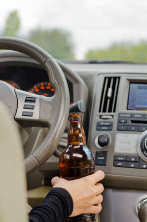 boozer: View inside a car from the back passenger seat of a woman driving holding a bottle of alcohol in one hand while steering