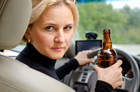 addictive drinking: Aggressive drunk woman driver holding a bottle of alcohol turning round in the drivers seat to glare into the back passenger compartment at the viewer