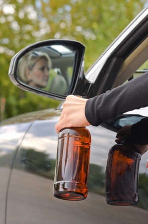 unlabelled: Drunk woman driver reflected in the side view mirror of the car dangling her arm through the open window clutching her bottle of booze