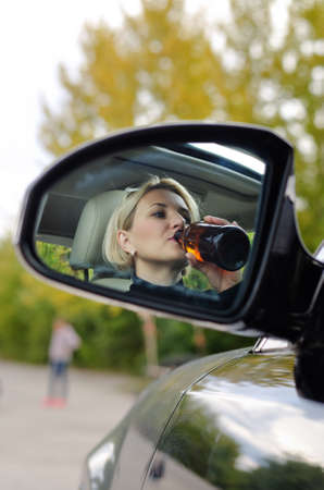 Reflection in the side rear view mirror of a drunk woman driver about to cause an accident drinking from an upended bottle and obscuring her view of a child up front on the road
