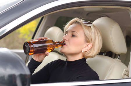 boozer: Woman alcoholic drinking from a bottle of alcohol as she drives the car