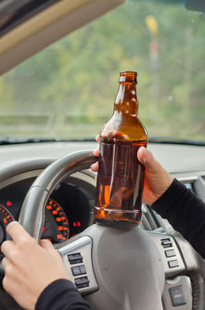 addictive drinking: Drunk woman driver with a bottle of booze resting it on the steering wheel as she drives along creating a road hazard for motorists through her diminished capabilities