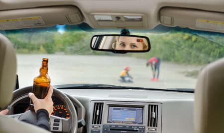 Verkeersongeval te wijten aan alcohol te gebeuren als een dronken vrouwelijke bestuurder geklemd haar fles drank in een hand tijdens het rijden benaderingen jonge kinderen die spelen in de weg Stockfoto