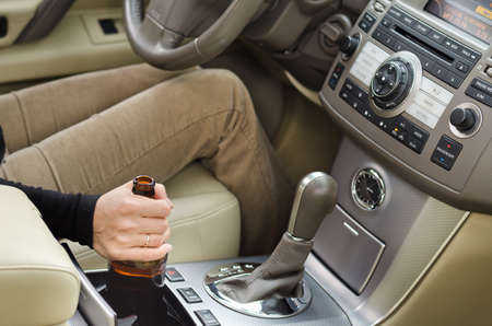 addictive drinking: Woman alcoholic holding a bottle of booze in the car with it balanced in the console as she drives along posing a danger to other motorists