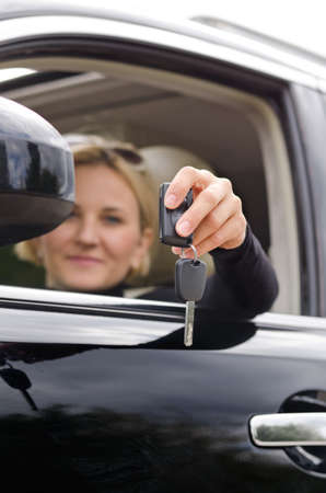 Smiling matured woman holding a car key photo