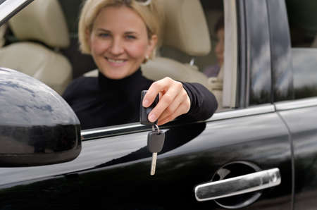 Attractive mature blond woman driver showing off the keys of a new car holding them out of the window with a proud smile photo
