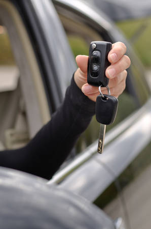 ownership and control: Car key with a remote control held through the open window of the vehicle in the hand of a woman